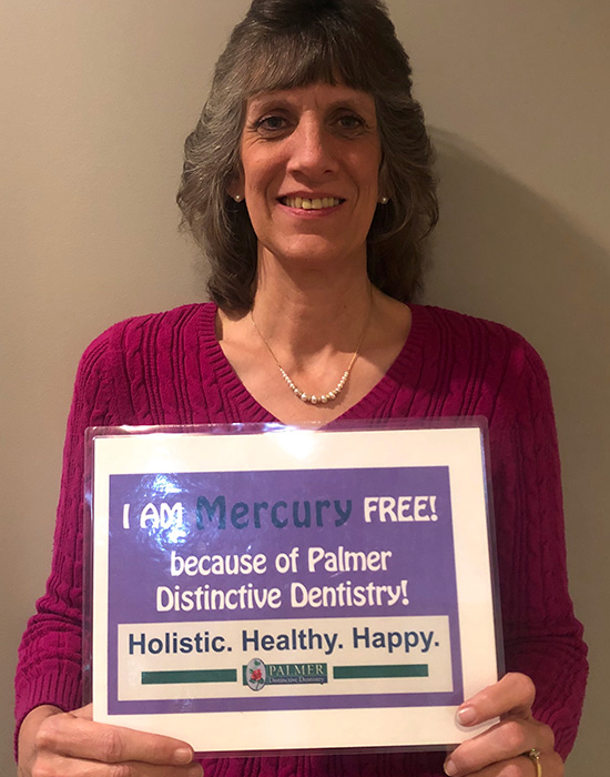 Smilling Matured Lady Showing Mercury Free Notice at Palmer Distinctive Dentistry in Greenville, Sc Area